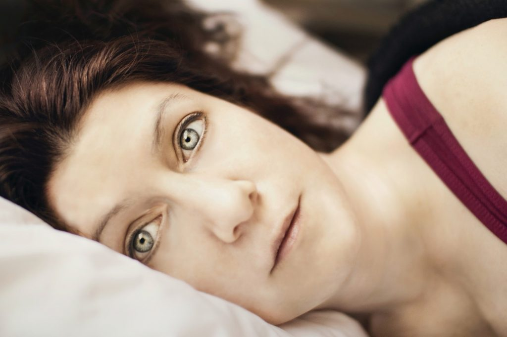 A close up of a woman lying on a bed