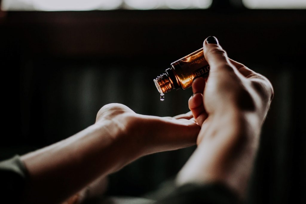 A close up of a hand and amber bottle